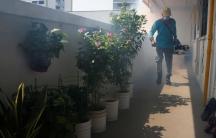 A worker fogs the corridor