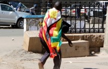 A man with a Zimbabwean flag wrapped around him throws stones