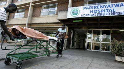 A man on a stretcher with a cast on his left leg is wheeled into a hospital's accident and emergency department