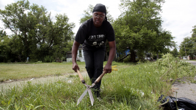 Rhonada Collier clears away tree branches in front of an abandoned house in an attempt to make her once thriving working-class neighborhood that is now littered with blight look better in Flint, Michigan.