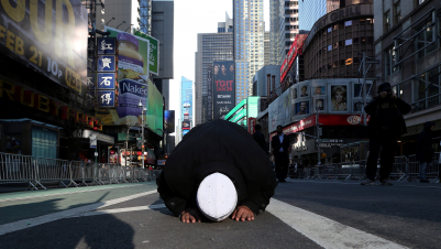 "A Muslim man kneels on Broadway Ave. as he takes part in afternoon prayers during an ""I am Muslim Too"" rally in Times Square, Manhattan, New York, Feb. 19, 2017."
