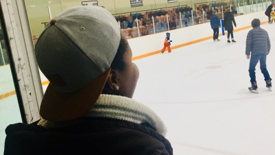 Close up of the back of a woman's head looking out onto a skating rink