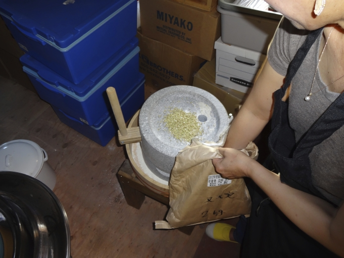 Sakai putting buckwheat into the mill.