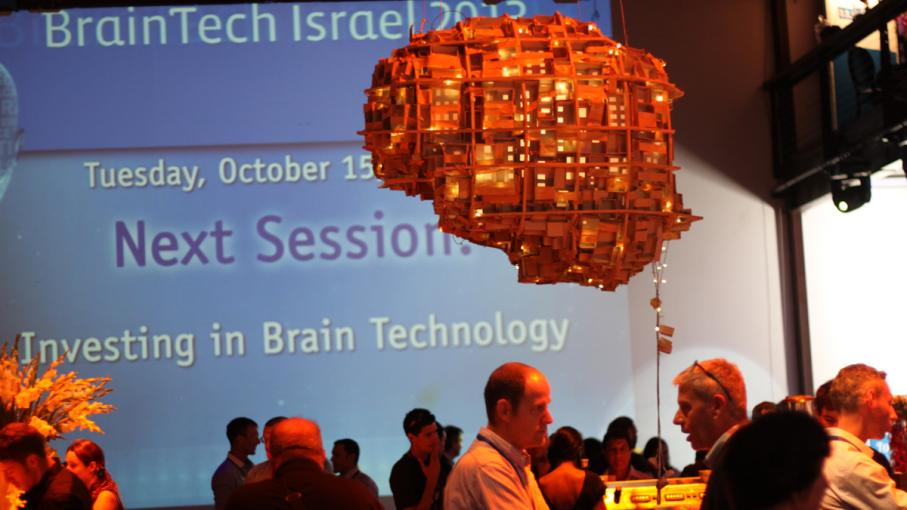 An artistic statue of the brain hovers over participants at the BrainTech conference in Tel Aviv.