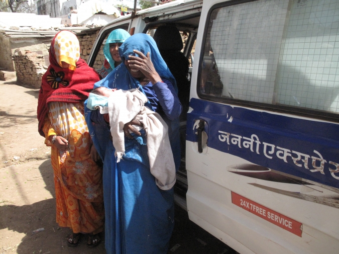 Jatav (left) and her mother-in-law (right, holding her granddaughter) prepare to step into the ambulance for the ride back to their village. The two women, accompanied by a village health worker, cover their faces because a regional custom forbids women t