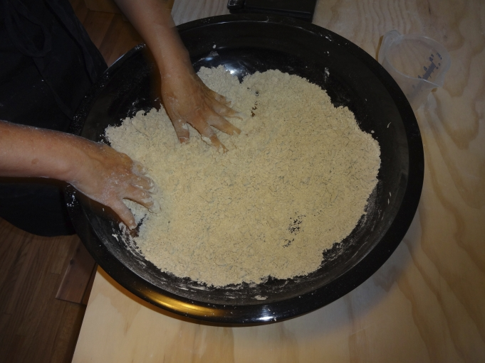 Mixing water and buckwheat flour to make soba noodles.