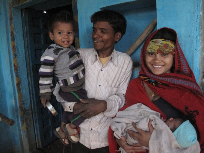 Jatav and her husband, 25 year-old Champalal Jatav, at home with their newborn daughter and their older son.