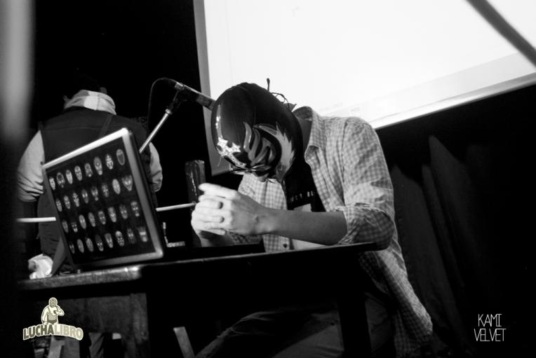 Masked writer Chicken Wilson struggling with a short story on stage at Lucha Libro in Lima.