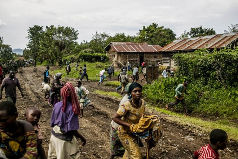 Congolese civilians scatter during a burst of heavy machine gun fire as FARDC troops advance toward Bunagana.