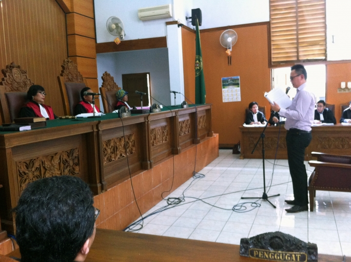 Benny Handoko reads his defense statement in front of a panel of judges in a Jakarta courtroom.