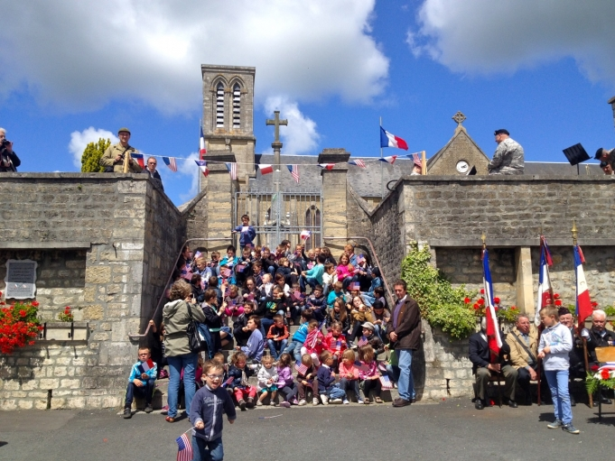 Children cheered and waved US and French flags to welcome veterans in the town of La Cambe.