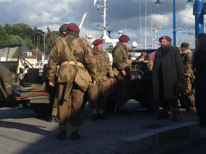 Men in period military fatigues walk around the streets of Port-en-Bessin during 70th Anniversary D-Day events.