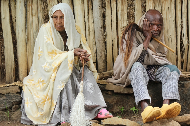 A man and woman outside Awra Amba's senior center. The village cares for its elderly collectively, an unusual practice in Ethiopia.