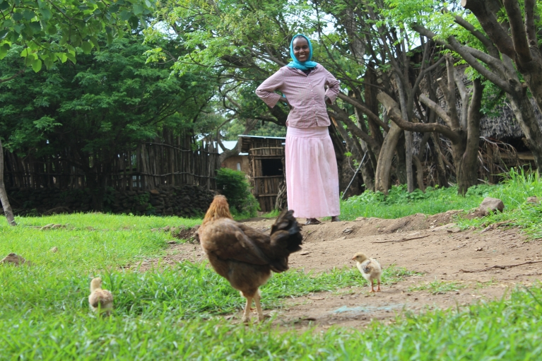 A woman tends to her chickens in Awra Amba.