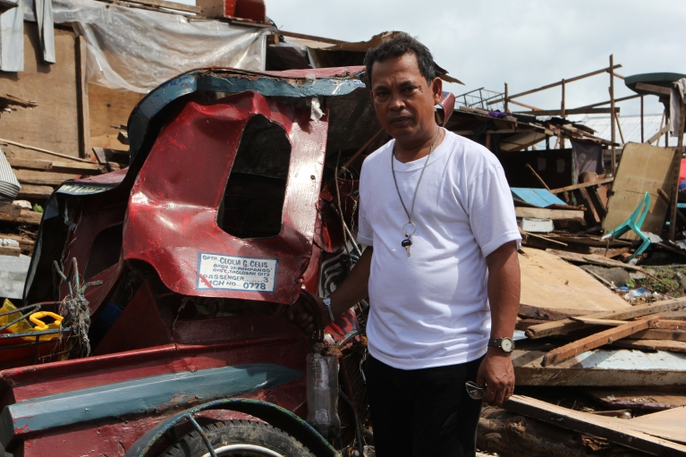 Rene Celis stands next to his tricycle, the standard form of public transport in Tacloban. Along with his late wife, Cecilia, Celis owned three tricycles, all of which were crushed by the storm surge.