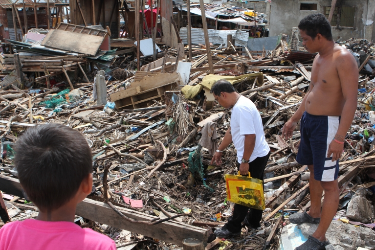 Rene Celis stands by a child's remains in the rubble. As neighborhood leader, it is his job to notify the authorities to recover the body.