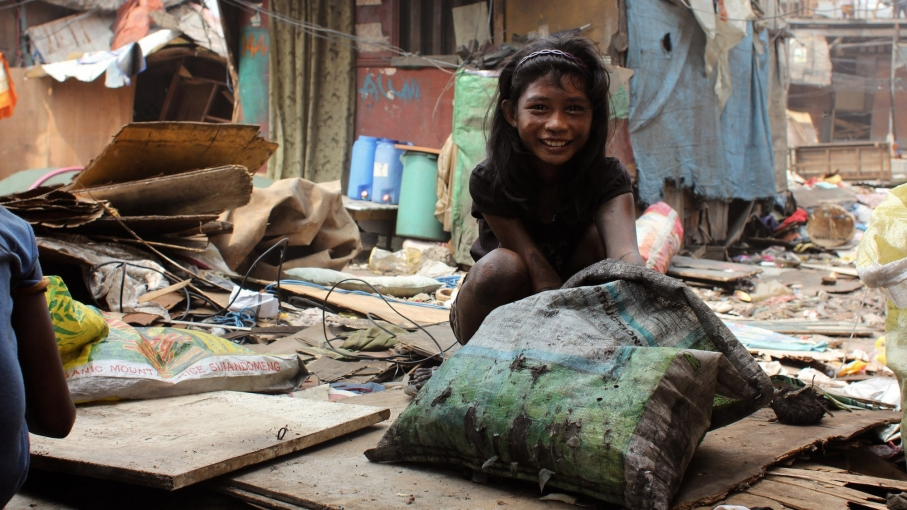 A young girl that lives in the shack next to Loste is covered in soot from hauling charcoal.