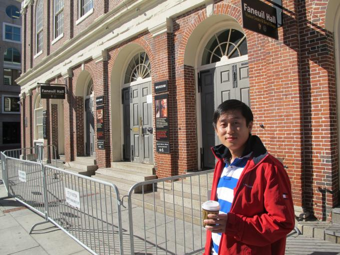 Jeff Li, a tourist from China, stands outside Boston's Faneuil Hall, where the visitor center is closed and informational brochures are cleared out.