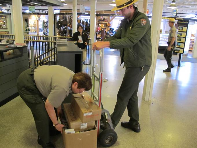 Employees at Faneuil Hall pack informational brochures in boxes, closing the information desk in the visitor center down.
