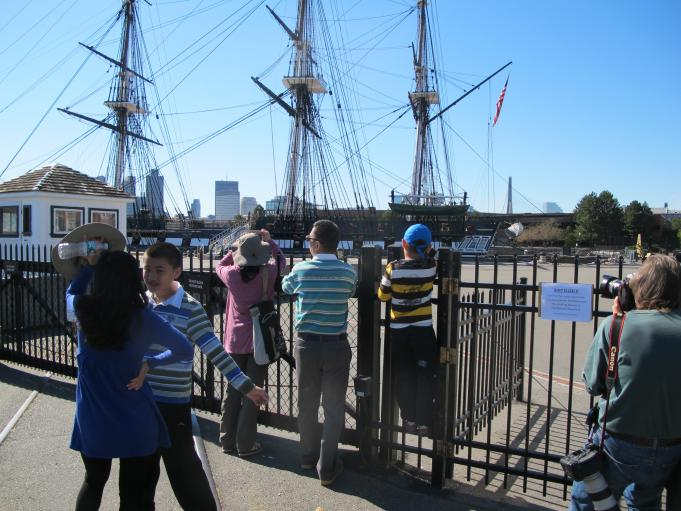 Tourists visiting from China look through the gate blocking the public from the USS Constitution.