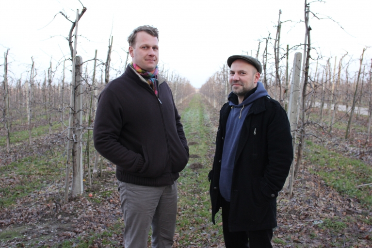 Marcin Hermanowicz and Tomek Porowski (right), in an apple orchard in an apple orchard in Ignacow. Marcin's family has been growing apples there for four generations.
