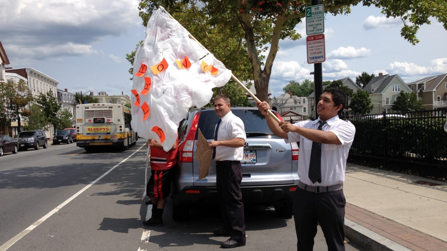 Kevin Perez-Barbosa waves a flag made of plastic grocery bags outside of the Market Basket in Somerville, Mass.