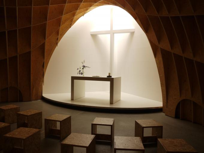 The wooden lattice dome creates an intimate space. Natural light filters in through a skylight above the altar.