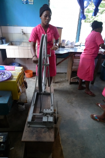 The clinic is famous for simple, locally constructed medical equipment. Here, a nurse operates a hematocrit centrifuge made from bicycle parts to separate plasma from red blood cells.