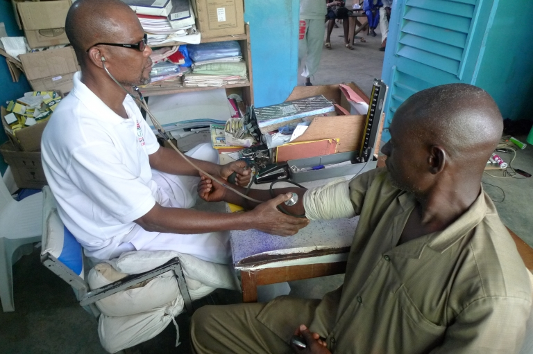 Head nurse A. Oyesomi takes a patient's blood pressure. The clinic treats 30,000 patients a year.