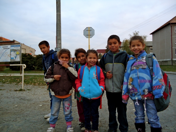Every day after school nearly 250 Roma students, including these first and second-graders, wait for an Ostrovany-bound bus in a grocery store parking lot.