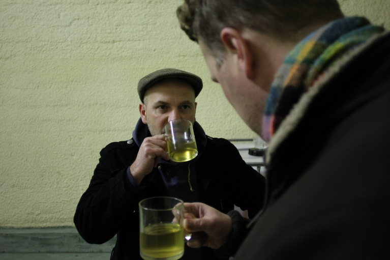 Tomek Porowski samples a batch of cider from 2013; it's still fermenting.