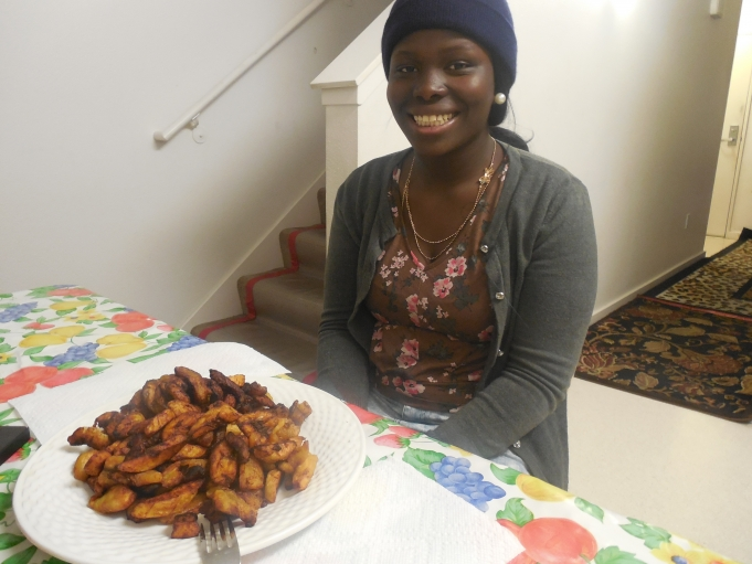 Patience Wilson, a Liberian refugee, prepares a traditional fried plantain dish. She said Christmas was a communal celebration when she lived in a refugee camp in the Ivory Coast.