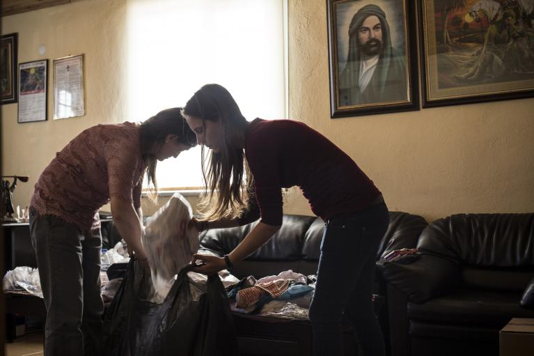 Turkish Alevi volunteers sort donations of underwear and undershirts in the offices of the Cemevi. A painting of Ali, revered by Shi'ite Muslims, of which Alevis are a sect, hangs on the wall. Alawites say they do not feel safe at Turkish refugee camps, w