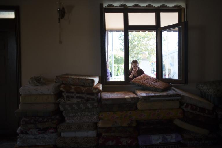 A Turkish woman looks into the worship area of the Cemevi, which is currently doubling as a storage place for mattresses, in order to accommodate Alawite refugees from Syria.