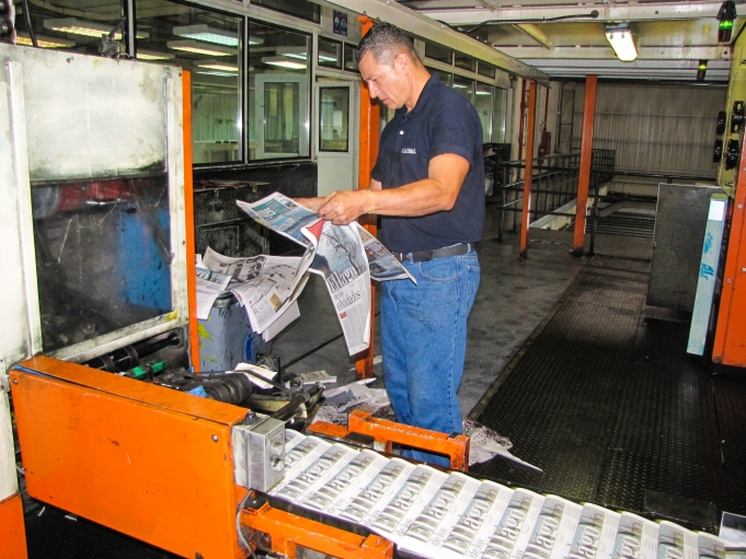 A technician at El Nacional technician scans what's left of the shrinking daily paper.