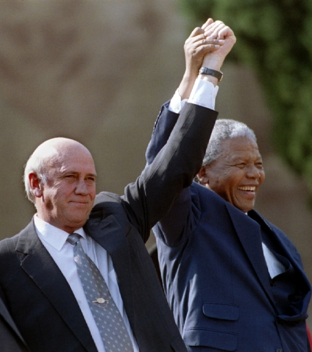 south african president nelson mandela and second deputy president fw de klerk hold their hands high as they address the huge crowd of people in front of