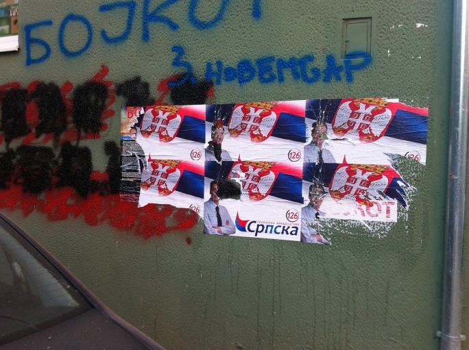 Campaign posters for the local elections, alongside a graffitied message to boycott them.