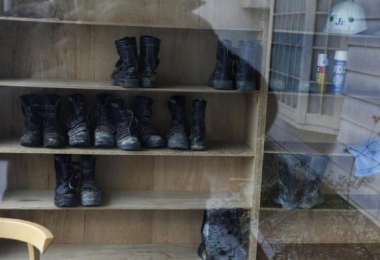 Workers' boots are seen through a window at Shuto Kogyo's dormitory for workers in Tome, Miyagi prefecture, December 20, 2013.