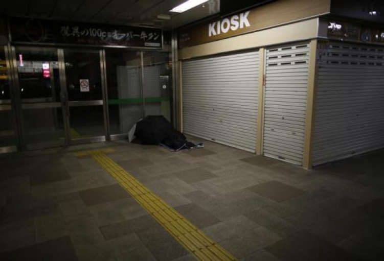 A homeless man rests on the ground at a concourse of Sendai Station in Sendai, northern Japan, December 17, 2013.