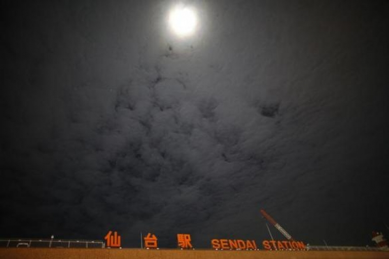 The signboard of Sendai Station is seen under the moonlight in Sendai, northern Japan, December 17, 2013.