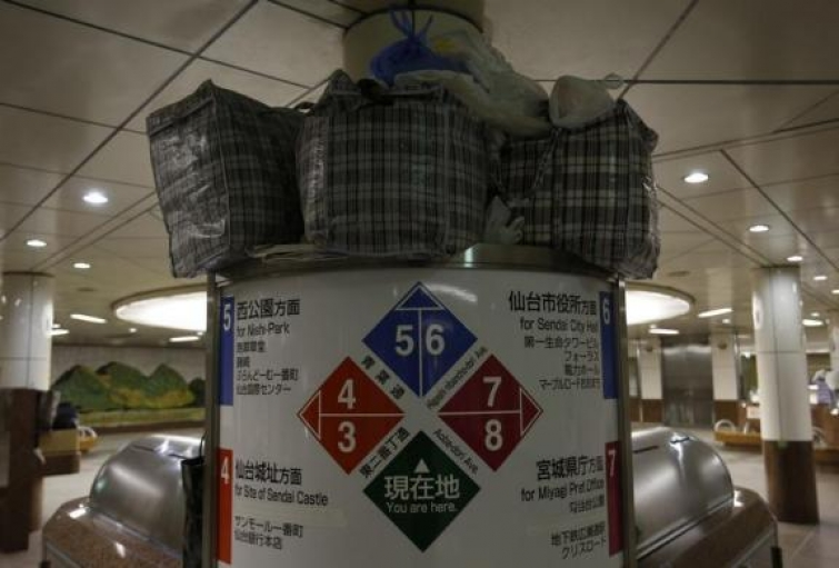 Plastic bags containing belongings of homeless men are placed on a signpost at an underground passage near Sendai Station in Sendai, northern Japan, December 17, 2013.
