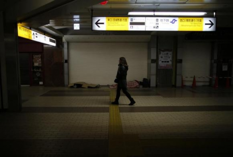 Shizuya Nishiyama (R), a 57-year-old homeless man from Hokkaido, and an another homeless man sleep on the ground as a passerby walks past at a concourse of Sendai Station in Sendai, northern Japan, December 17, 2013.