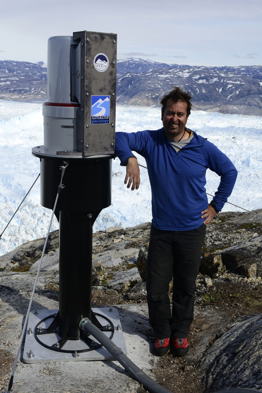 Glaciologist Gordon Hamilton from the University of Maine standing next to a new state-of-the-art laser his team has just installed on the rim of Greenland's Helheim glacier. The laser will scan the glacier in unprecedented detail and provide valuable clu
