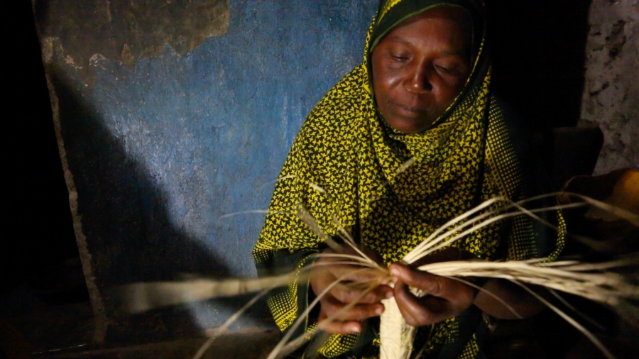 Kanoa Sharif Haji, a 45 year old mother of eight, weaves reed mats at night under a bright solar powered LED light at her home in Matemwe. This new work at night earns her family an extra fifteen dollars a month, a huge amount in these parts.