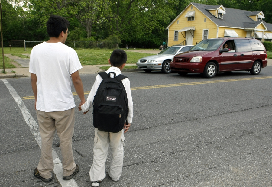 Young man holds hand of boy with backpack, crossing a street