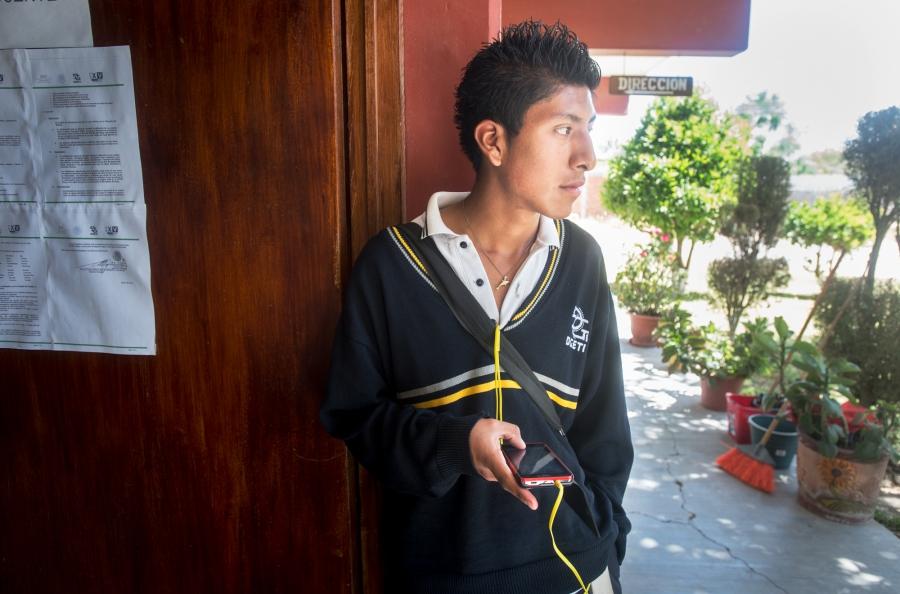Student with headphones in outdoor school hallway