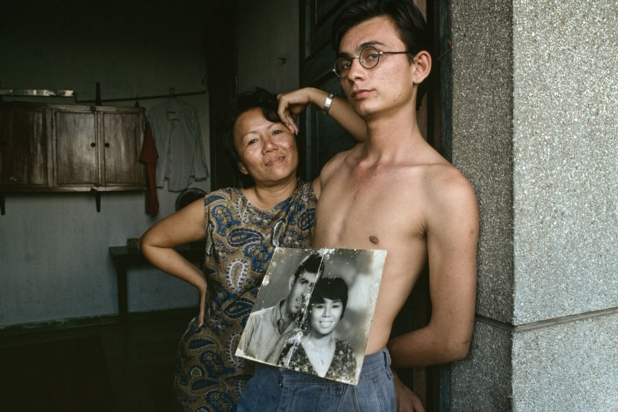 A mixed-race young man with a faded black and white photo of his parents: a handsome American GI and his Vietnamese bride.