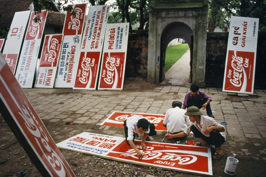 "A group of men painting Coca-Cola logos on a dozen signboards. In the 1990s Vietnam revised its constitution to allow the practice of ""private capitalism."""