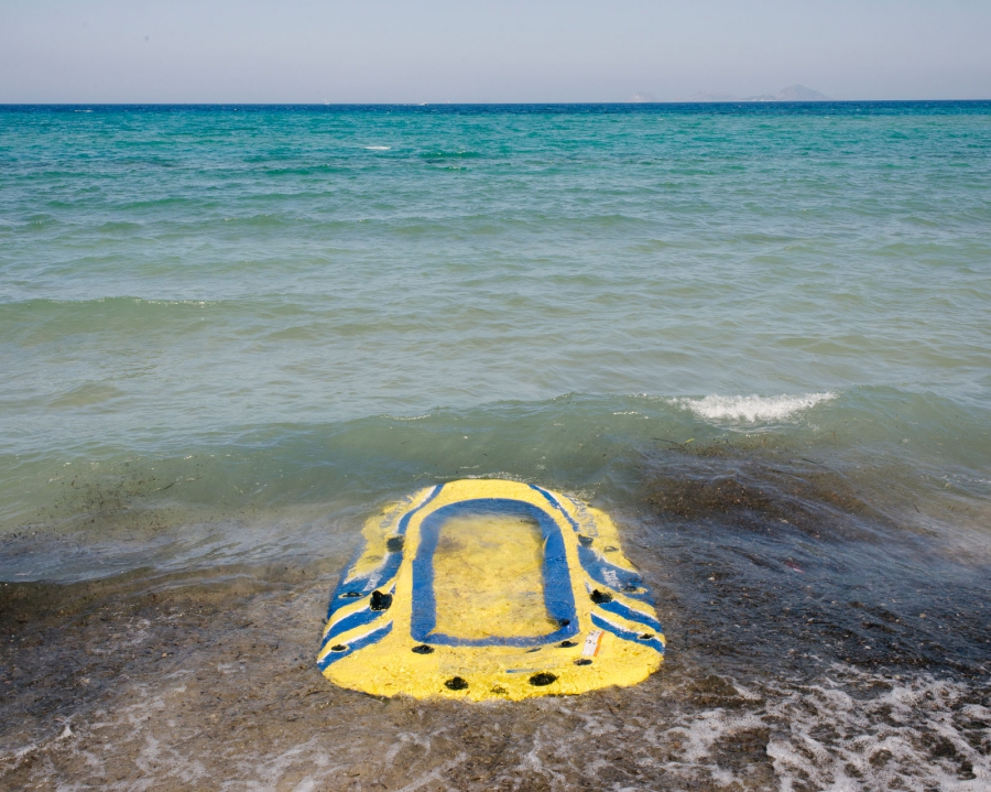 """Tourists vs. Refugees"" - a rubber raft is deflated at the beach."