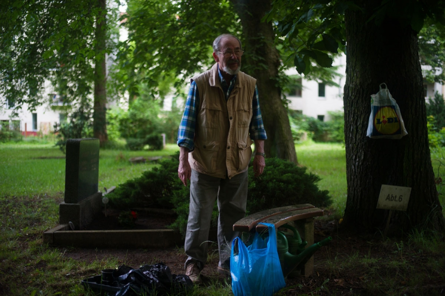 Pensioner Matthew Smith pauses from his cleanup work in a cemetery of Berlin's Jerusalem Church a Sunday afternoon. Smith says he comes to the cemetery regularly to tend to his son's grave. The church's plans to use the cemetery for new public spaces does